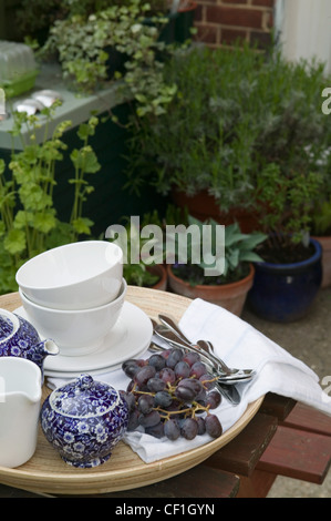Renovated Flat Tea tray on wood table on the patio and potted plants in background - Stock Photo