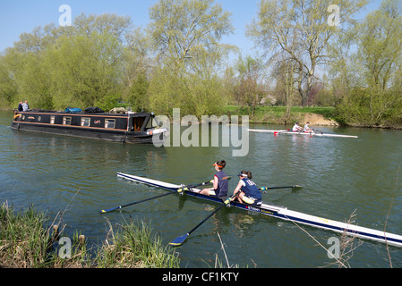 Two double sculls and a barge on the River Thames at Abingdon. - Stock Photo
