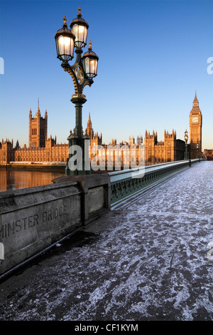 An icy pavement over Westminster Bridge looking towards Big Ben and the Houses of Parliament at sunrise in winter. - Stock Photo