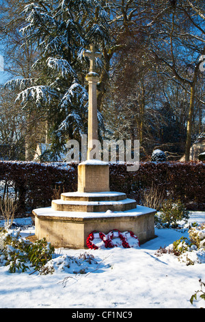 Winter view of the stone war memorial cross in the Cotswold village of Ampney Crucis, Gloucestershire, England, - Stock Photo
