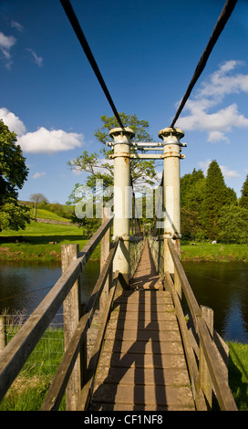 Suspension Bridge over the River Wharfe on the Dales Way Long Distance Path at Hebden in the Pennines. - Stock Photo