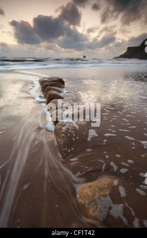 Waves rushing onto the beach at Saltwick Bay. - Stock Photo