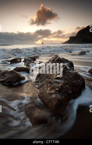 Waves rushing onto the beach at Saltwick Bay. - Stock Photo