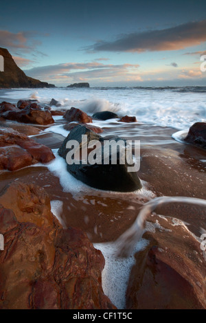 The tide flowing onto the beach at Saltwick Bay. - Stock Photo