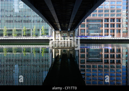 Reflection from buildings, part of the Canary Wharf development in West India Millwall Docks on the Isle of Dogs - Stock Photo