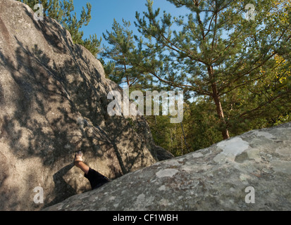 A climbers chalked arm is visible between boulders with shadows of the trees in pattern in sunlight in a forest - Stock Photo