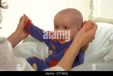 Baby sitting on pillows on bed hands held by female off camera - Stock Photo