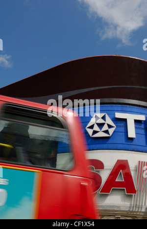 The top of a red London double decker bus passing advertisements in Piccadilly Circus. - Stock Photo