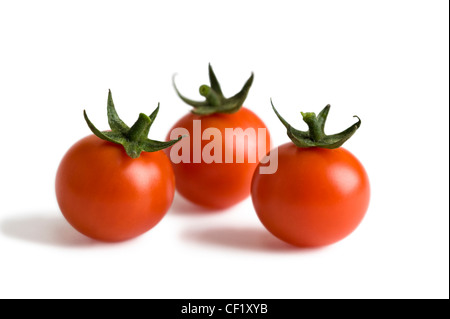 three cherry tomatoes isolated on a white background - Stock Photo