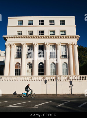 A man cycling using a 'Boris Bike' past a 19th century stuccoed building designed by architect John Nash in Cumberland - Stock Photo