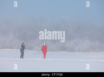 Elderly man and woman cross-country skiing , Finland - Stock Photo