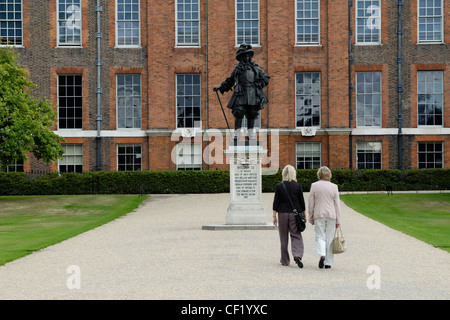 Two tourists walking towards the statue of William III in front of Kensington Palace. Kensington Palace was originally - Stock Photo