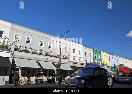 a black london taxi cab passing a row of shops and restaurants in westbourne grove
