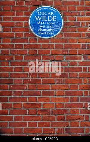 A London County Council blue plaque on the wall of a building celebrating Oscar Wilde 1854 - 1900, wit and dramatist, - Stock Photo