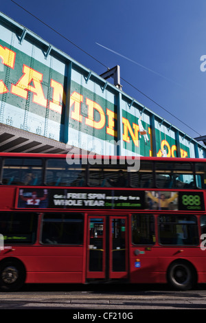 A red double decker bus passing under the old railway bridge over Chalk Farm Road at Camden Lock. The bridge features - Stock Photo