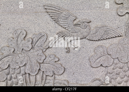 Bird carved on stone wall in chinese temple Thailand - Stock Photo