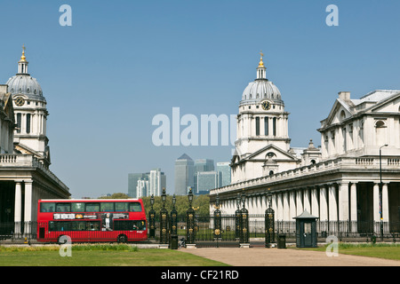 A red double decker bus passing the Old Royal Naval College in Greenwich with the skyscrapers from Canary Wharf - Stock Photo