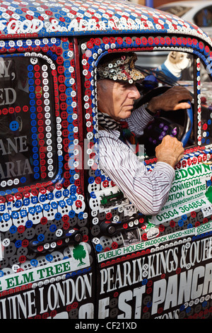 A taxi driver in a Pearly Kings and Queens decorated London taxi cab. - Stock Photo