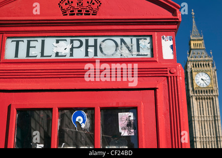 A red telephone box with Big Ben in the background. - Stock Photo