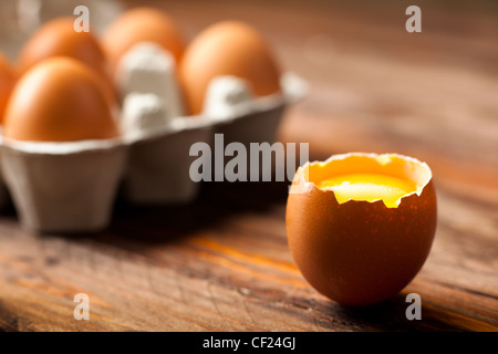 Opened Egg Shell with Yolk on Wood - Stock Photo
