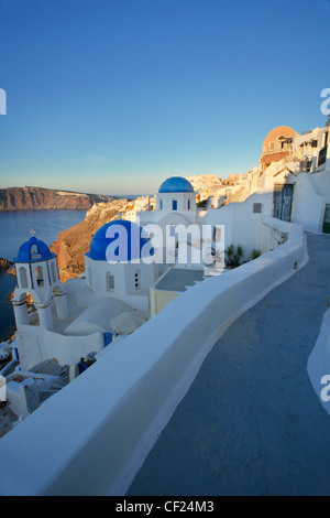 A view from a little path over some blue domed Greek Orthodox churches in the village of Oia on Santorini - Stock Photo