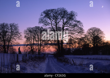 The sun sets behind a country track covered by a winter snow fall. - Stock Photo