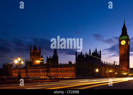 Light trails from traffic passing over Westminster Bridge with Big Ben and the Houses of Parliament in the background. - Stock Photo