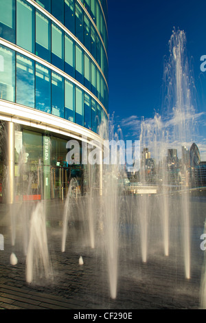Water fountains near City Hall and the 'More London' development on the south bank of the River Thames, looking - Stock Photo