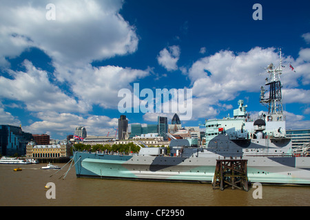HMS Belfast, originally a Royal Navy light cruiser, permanently moored in London on the River Thames with the City - Stock Photo