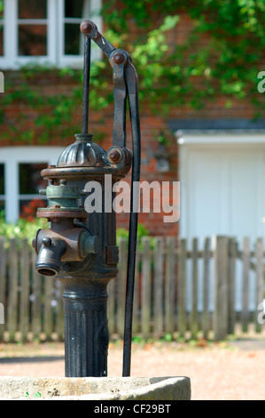 Old water pump with cottage in background at Hambleden Village. The name is Anglo Saxon in origin and means 'crooked - Stock Photo