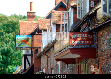 Pub and butcher signs with houses at Hambleden Village. The name is Anglo Saxon in origin and means 'crooked or - Stock Photo