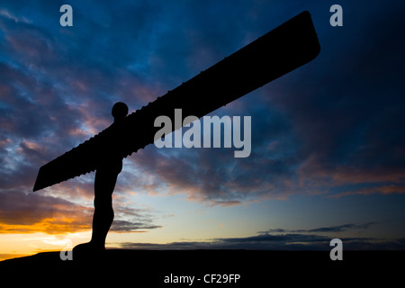 The iconic Angel of the North statue silhouetted against an atmospheric sky. The 'Angel', built on a a former colliery - Stock Photo