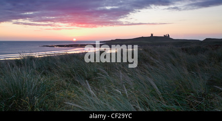 Sunrise over the ruins of Dunstanburgh Castle on the wild Northumberland coast. - Stock Photo