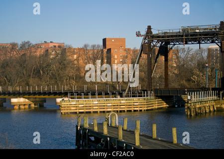 A CSX railroad bridge crossing over the Anacostia River and boat dock in Washington DC - Stock Photo