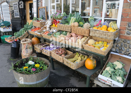 Fruit and vegetables for sale outside a traditional village grocery shop. - Stock Photo