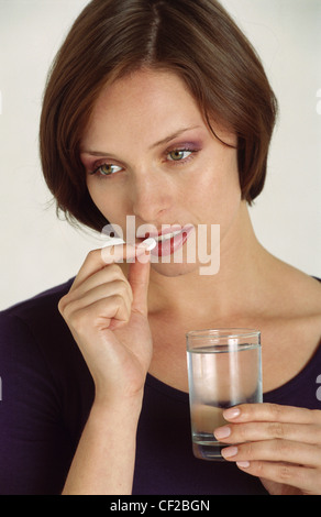 Female short brunette hair suffering from pain taking tablet, holding a glass of water in one hand, unsmiling, looking - Stock Photo