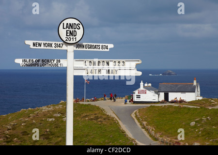 Lands End milepost with the First and Last house in the background. - Stock Photo