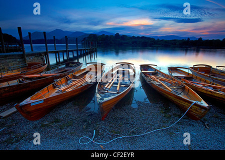 Rowing boats on the shore of Derwentwater next to Keswick Jetty at sunset in the Lake District National Park. - Stock Photo