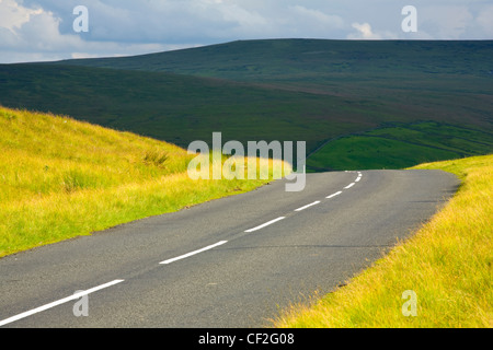 A country road running through dramatic Pennine scenery, in the North Pennines Area of Outstanding Beauty. - Stock Photo