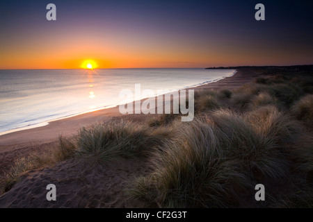 Blyth Beach and sand dunes at sunrise, looking south towards Seaton Sluice. - Stock Photo