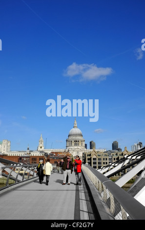 People crossing the Millennium Bridge over the River Thames connecting Bankside on the south bank to St Pauls on - Stock Photo