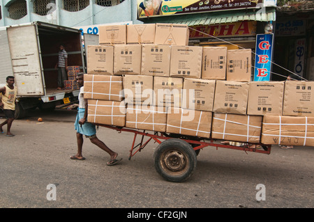 carrying a big load in the Pettah market in Colombo, Sri Lanka - Stock Photo