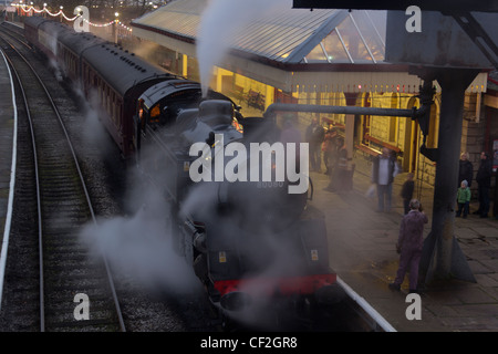 Standard Class 4 tank engine 80080 stands at Ramsbottom station at dusk  on the East Lancashire  Railway. - Stock Photo