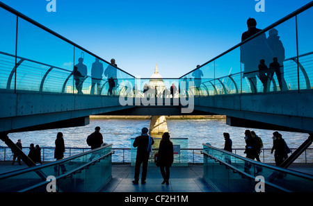People walking on the Millennium Bridge at Bankside looking towards St Paul's Cathedral on the north bank of the - Stock Photo