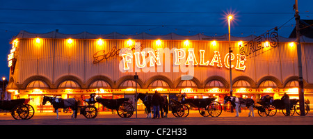 Hackney Carriages outside the Fun Palace amusement arcade on the Golden Mile. - Stock Photo