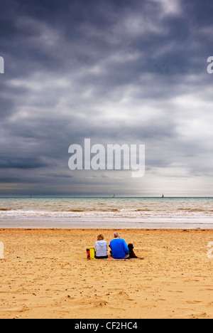 A couple sitting with their dog under a gloomy sky on the beach at Camber Sands.