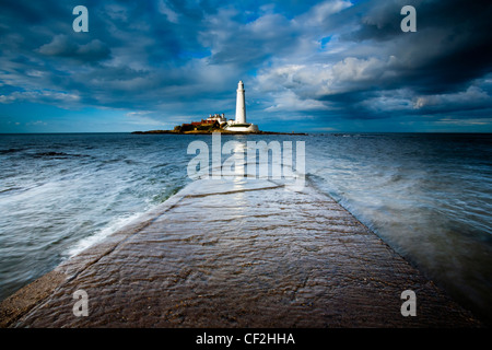 Incoming tide engulfs the causeway linking St Mary's Island & lighthouse to the mainland. - Stock Photo