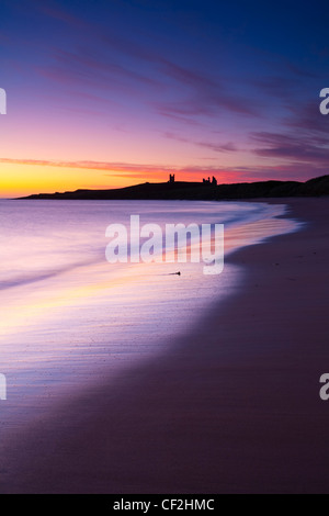 A colourful display of pre-dawn colours relected upon the wet sands of Embleton Bay, overlooked by the dramatic - Stock Photo