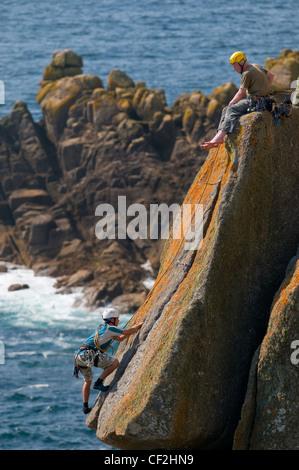 Rock climbing on the coast of Gwennap Head in Cornwall. - Stock Photo