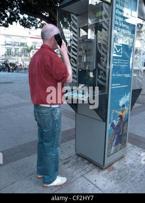 Man using a public telephone in the Plaza de la Constitucion, Fuengirola, Costa del Sol, Andalucia, Spain, Western - Stock Photo